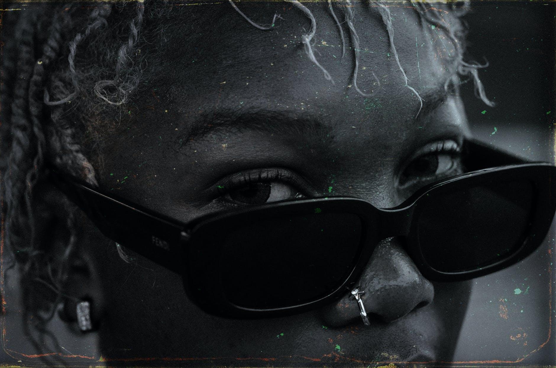 crop black woman in stylish sunglasses on street